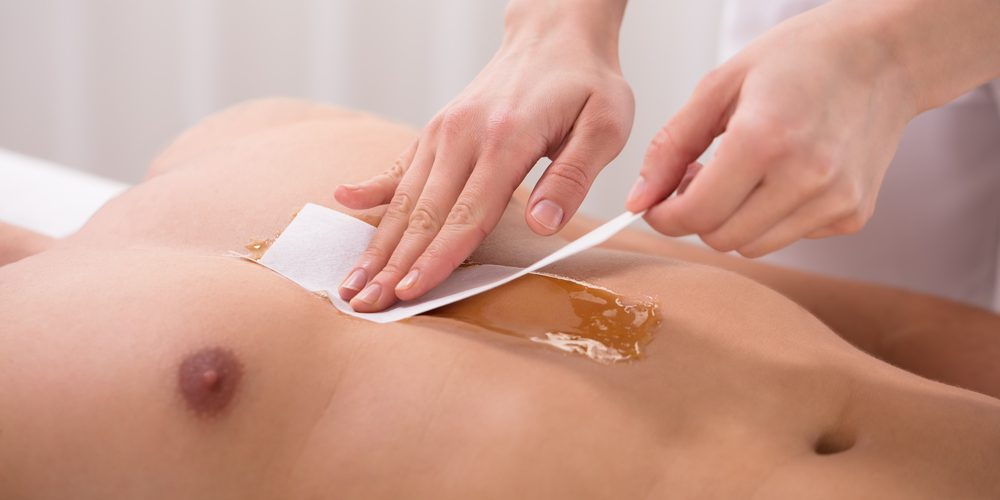 Therapist's Hand Waxing Man's Chest With Wax Strip