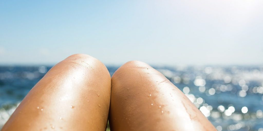 smooth-tanned-female-legs-in-the-spray-of-water-on-the-beach-against-the-background-of-the-sea_t20_4dzeXa